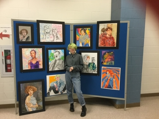 BHS Art student Mary Miller standing in front of her various art pieces displayed on a wall.